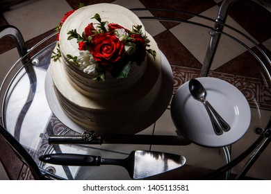 top view on wedding cake on glass tray with plates and spoons