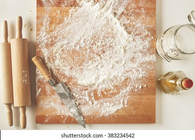 Top view on white table with isolated wooden board with knife, two rolling pins, bottle olive oil, transparent jar with flour. Presentation cooking process
