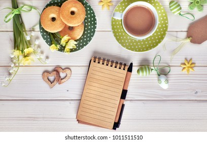 Top view on white wooden table with espresso cup, plate of cookies, Easter eggs and spring flowers. Springtime coffee concept, text space