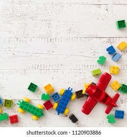 top view on white wooden table background with colorful plastic toy bricks and details.