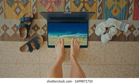 Top view on woman bored at home during coronavirus quarantine lockdown. Sad and bored look forward to vacation, put feet in imaginary beach sand on laptop. Concept cancelled summer holiday