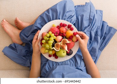 Top view on woman sitting cozy on the couch and enjoying delicious summer fruit and berries. Girl holding white plate with apricots, raspberries, peaches and figs on her knees. Healthy eating.