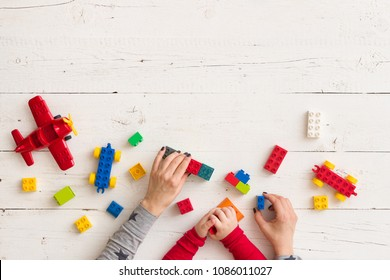 Top view on woman's and child's hands playing with plastic bricks and small toy and details on white wooden table background
