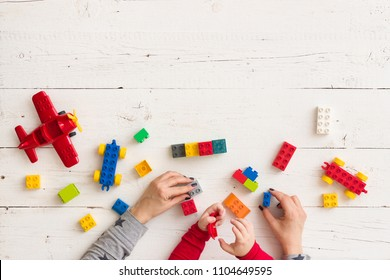 Top view on woman's and child's hands playing with colorful toys, wheels, part, plastic bricks and details on white table background