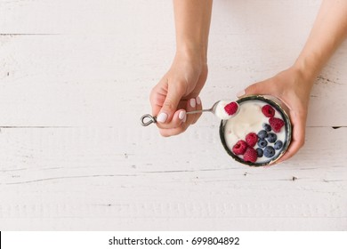 Top view on woman's hands holding small bowl with organic yogurt with blueberries and raspberries on white wooden background. Girl having healthy breakfast at home. Healthy eating, snack.