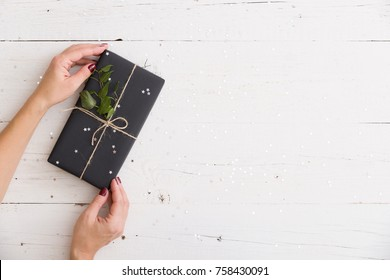 Top view on woman's hands with Christmas, birthday or any other celebration gift wrapped in  black paper and decorated with twine, silver sparkling stars and tree branch on white wooden background.