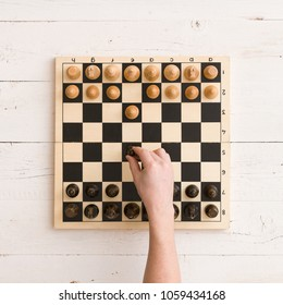 Top view on wooden chess board with chess figures ready for the game and man's hand making chess move on white wooden table background