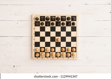 Top view on wooden chess board with figures during the game on white wooden table background. First chess move.