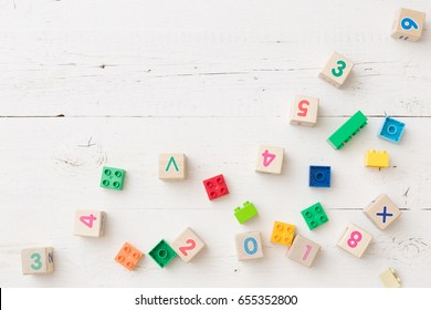 Top view on wooden cubes with numbers and colorful plastic bricks on white wooden table background. School, education and learning concept.