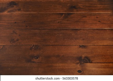 Top view on wooden planks of dinner table polished and tied each to other solidly, rich wooden textured background
