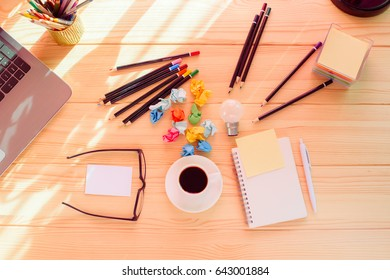 Top view on wooden table with coffee, pencils, colorful papers and notebook and laptop