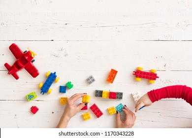 Top view on young woman's and child's hands playing with toys and plastic bricks on white wooden table background. Learning by playing.