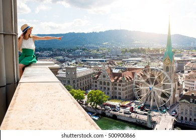 Top view on Zurich city with young woman showing sitting on the tower's top. Woman having a great vacation in Switzerland