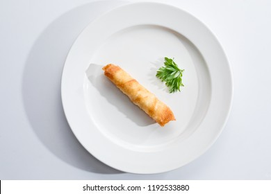 Top view of a one Cigar Pastry on a white plate and background.
