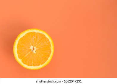 Top view of a one orange fruit slice on bright background in orange color. A saturated citrus texture image