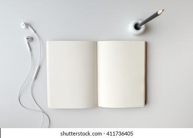 Top view open blank notebook, earphone, and pencil in holder on white desk background