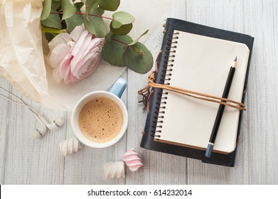 Top view of open blank notebook, bouquet, flower, cup of coffee, earphones. Travel and adventure concept, journey diary