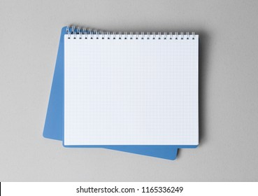 top view of a open blue notebook on a gray background, school notebooks with a spiral spring, office notepad flat lay