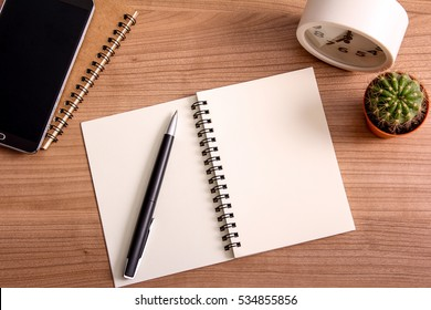 top view of open book with pen, clock, smartphone and cactus in pot on wooden desk