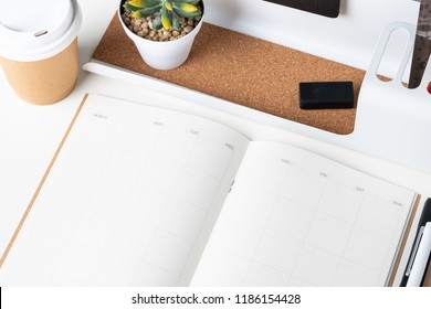 top view of open calendar planner with modern office stationery and take away coffee cup on white desk in office. mock up space of organizer table notebook