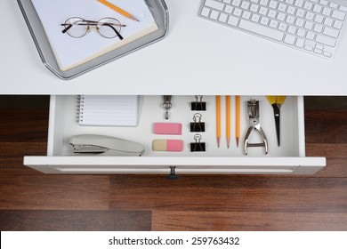 Top view of an open desk drawer showing the organized items inside. The top of the desk has a computer keyboard and wire in-box with paper and pencil. The drawer has pencils, erasers, stapler and more
