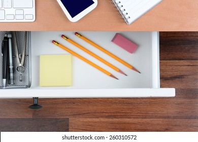 Top view of an open desk drawer showing the items inside. The top of the desk has a computer keyboard Cell Phone and note pad. The neat drawer has pencils paper and organizer.