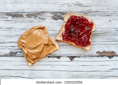 Top view of open face homemade peanut butter and strawberry Jelly sandwich on oat bread, over a white rustic wooden table / background.
