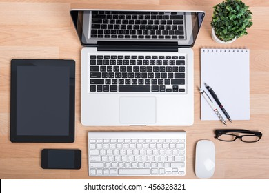 Top view open laptop with digital tablet and white smartphone on wooden desk