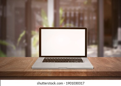 Top view of open laptop or notebook isolated on wooden table in soft blurry restaurant background. of free space for your copy, view from top.