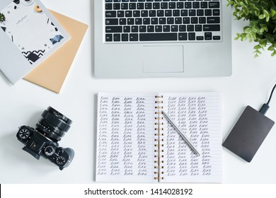 Top view of open notebook with blah blah notes and pen, photocamera, laptop keypad and copybooks on workplace of photographer