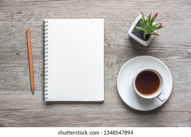 Top view open notebook with blank pages and coffee cup on wooden background