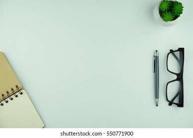 Top view of open notebook, pen, eye glasses and plant on white background. Business planning concept.
