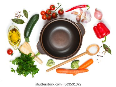 Top view of open pan, fresh raw vegetable and spices for soup isolated on white background