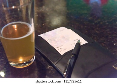 Top view open pint glass beer next to leather bill holder with restaurant check and pen. Close-up, soft focus receipt total amount on marble table at bar, pub counter. Customer payment for beverage