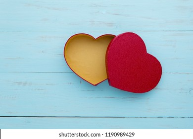 Top view of an open red gift box shaped a heart symbol on the wooden table