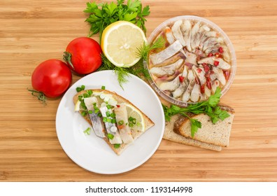 Top view of the open sandwich with slices of pickled Atlantic herring fillet, lemon and green onion on a saucer among of ingredients for its preparation on a bamboo wooden surface
