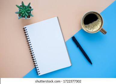 Top view of open school notebook with blank pages and pen with coffee cup on light-blue brown two-tone background. Flat lay, creative workspace office. Business or education concept with copy space.