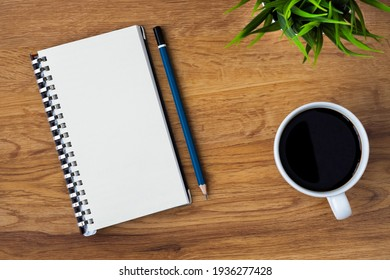 Top view of open school notebook with blank pages, coffee cup and pencil for taking write notes on table background. Flat lay, creative workspace office. Business-education concept with copy space.