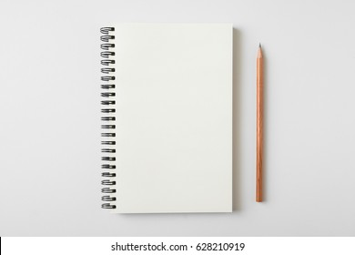 Top view of open spiral blank notebook with wood pencil on white desk background