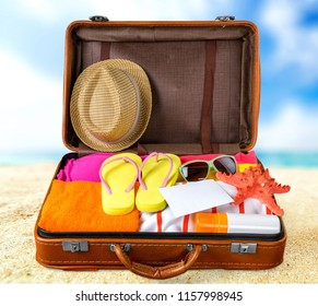 top view of an open suitcase with full of summer stuff on blue background