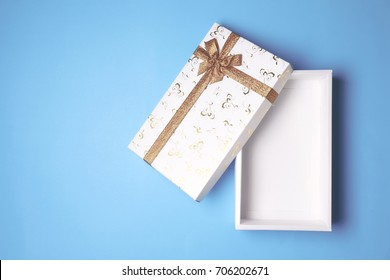 Top view of open white gift box on blue background. Free space for text