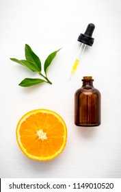 Top view of orange, bottle and dropper on white wooden table background in concept pure orange extract.Vitamin C,full flavoured,ingredient for food,cake,drinks and spa product.Best natural skin care.