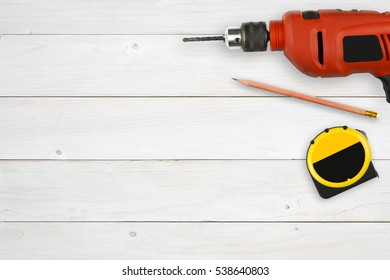 top view orange drill, pencil with rubber and yellow measuring tape for carpenter or labor day on white vintage wood table or floor with copyspace for your object or text