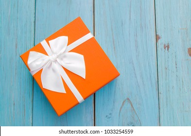 Top view of orange gift box with ribbon on wooden vintage background for birthday.