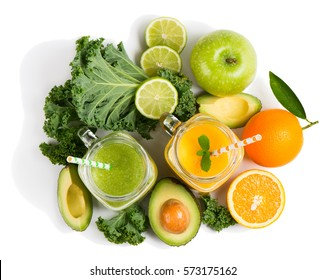 Top view of orange and green smoothie with ingredients on white:  avocado, apple, kale, orange, lime. Isolated on white background.