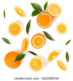 Top view of orange juice in a glass and whole and slices of orange fruits with green leaves isolated on white background.