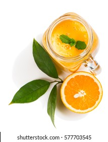 Top view of orange smoothie and slice orange fruit with green leaves isolated on white background.