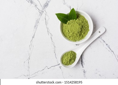 Top view of organic green matcha tea?powder in bowl on white marble background with copy space