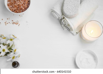 Top view of organic spa skincare products with salt, candle, flowers, essential oil,face cream, towels and pumice stone