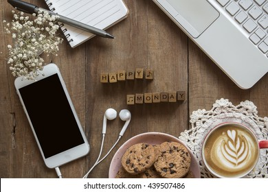 Top view of organized working space at the home office with letter spelling the word Happy Monday,blank screen cellphone, A cup of coffee with art latte,earplugs,cookies on wooden background ,flat lay